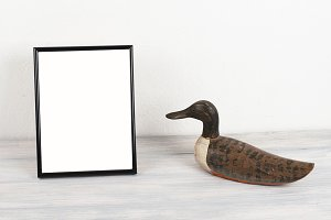 Photo frames next to wooden duck on wooden table. Decor.