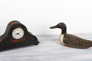 Antique wooden clock next to figure of a duck on wooden table.