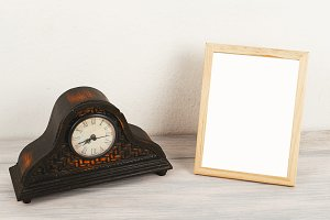 Photo frames next to wooden clock on wooden table. Decor.