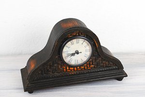 Wooden clock on wooden table. Decor.