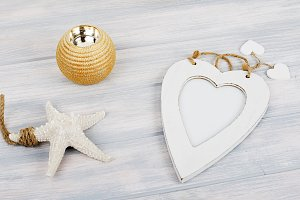 Photo frames with heart shape on wooden table next to decorative objects. Decor.