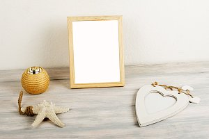 Photo frames on wooden table next to decorative objects. Decor.