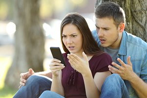 Angry couple using a smart phone