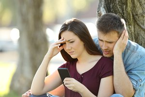 Worried couple using a smart phone