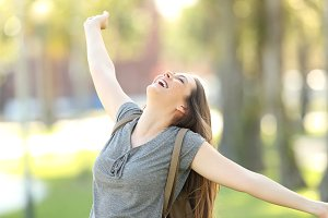 Excited happy girl raising arms