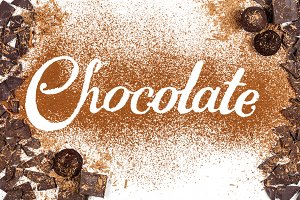 The word Chocolate written by cocoa powder with dark chocolate and candies