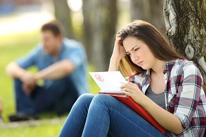 Sad student looking at failed exam