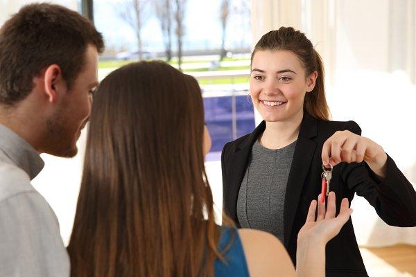 Real estate agent giving home keys
