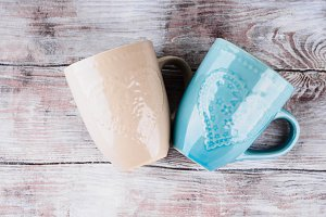 Two ceramic cups with hearts on wooden background