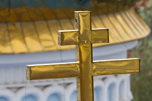 Golden orthodox cross on dome of church