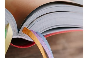 Closeup of the back of a book with colored bookmarks.