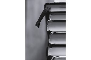 Top view of a stack of books. Black and white photography.