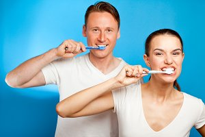 Man And Woman Brushing Their Teeth