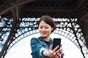 Young Chinese Female Tourist In Front Of The Eiffel Tower