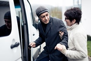 Nurse Helping Senior Man Enter A Van