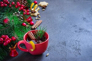 Mulled wine in red mugs and Christmas festive background