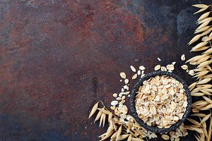 Oat flakes and spikelets on rusty background