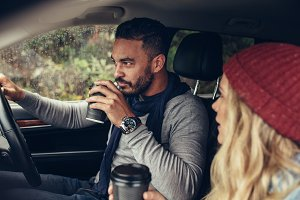 Couple drinking coffee while driving