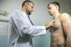 Doctor examining young male patient with stethoscope. Medical worker listening heartbeat of athletic man. Medic checking chest of guy in her office at the hospital. Close up