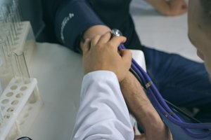 Male doctor checking blood pressure to young man. Pulse measurement to patient