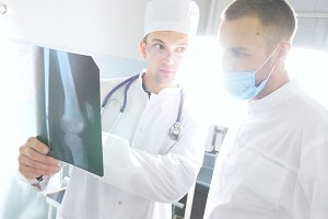 Male medics consult with each other while looking at x ray image. Medical workers in hospital examine x-ray prints. Two caucasian doctors view mri picture and discussing about it