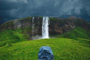 Hiker woman walking under the waterfall in Iceland