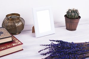 Photo frames next to decorative objects, books and lavender flower on white and blue wood table. Decor.