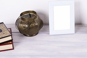 Photo frames next to decorative objects and books on white and blue wood table. Decor.