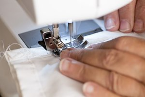 Mature woman hands using sewing machine.