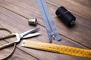 Scissors, tape measure, zipper, thread and needle next to thimble on wooden table.