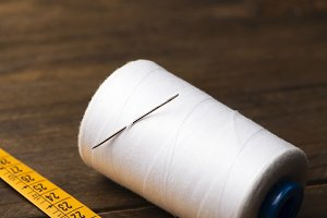 White bobbin of thread, needle for sewing and tape measure on wooden table.