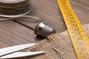 Scissors, tape measure, thread and needle next to thimble on wooden table.