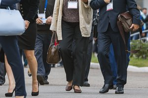 Businesswomen and businessmen walking along street at conference or exhibition