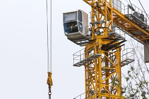 Construction crane - yellow metal tower and white cabin - close up