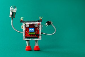 Robot with light bulb lamp in hand. Fun toy character on green background, copy space