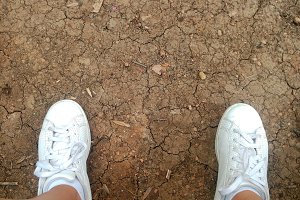 Dirty Cracked Soil with sneakers