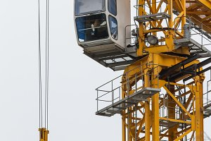 Construction crane - yellow metal tower and white cabin - vertical