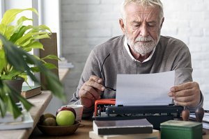 Elderly is using typewriter