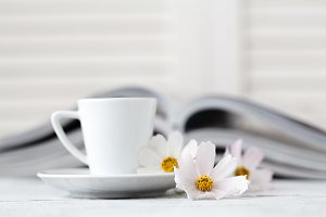 cup of tea on book with flower.