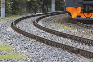 Curving railway tracks on crushed stone and orange train, telephoto