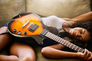 woman sleeping on couch with guitar
