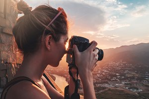 Female photographer, taking pictures of mountain landscape at sunset