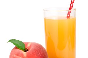 Glass of fruit juice with straw and cut peaches isolated on white background