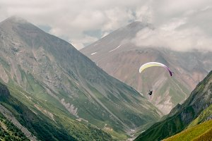 Paraglider in the green mountains