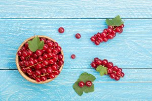 Red currant berries in a wooden bowl with leaf on the blue wooden background. Top view