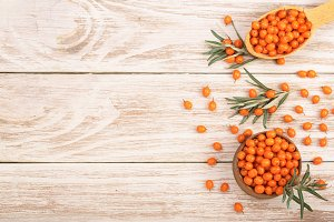 Sea buckthorn. Ripe fresh berries in bowl on white wooden background with copy space for your text. Top view