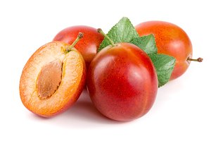 red plums end half with leaves isolated on white background
