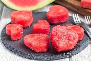 Slices of fresh seedless watermelon cut into heart shape on slate board, horizontal