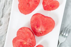 Slices of fresh seedless watermelon cut into heart shape on white plate, flat lay, vertical