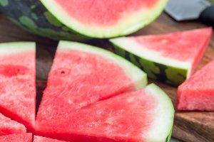 Slices of fresh seedless watermelon cut into triangle shape on wooden plate, vertical